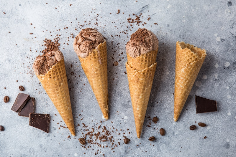 four waffle cones laying on a stone surface, three of the cones have scoops of chocolate ice cream