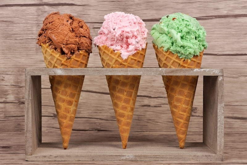 three waffle cones in a rack with chocolate, strawberry, and pistachio ice cream
